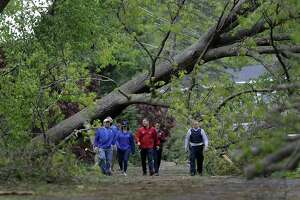 """A National Weather Service team, including meteorologist Bill Goodman, far left, tours Brookfield along with State Police on Wednesday to assess damage from Tuesday's storm. The team concluded that the damage was most likely caused by a """"macroburst"""" than a tornado."""