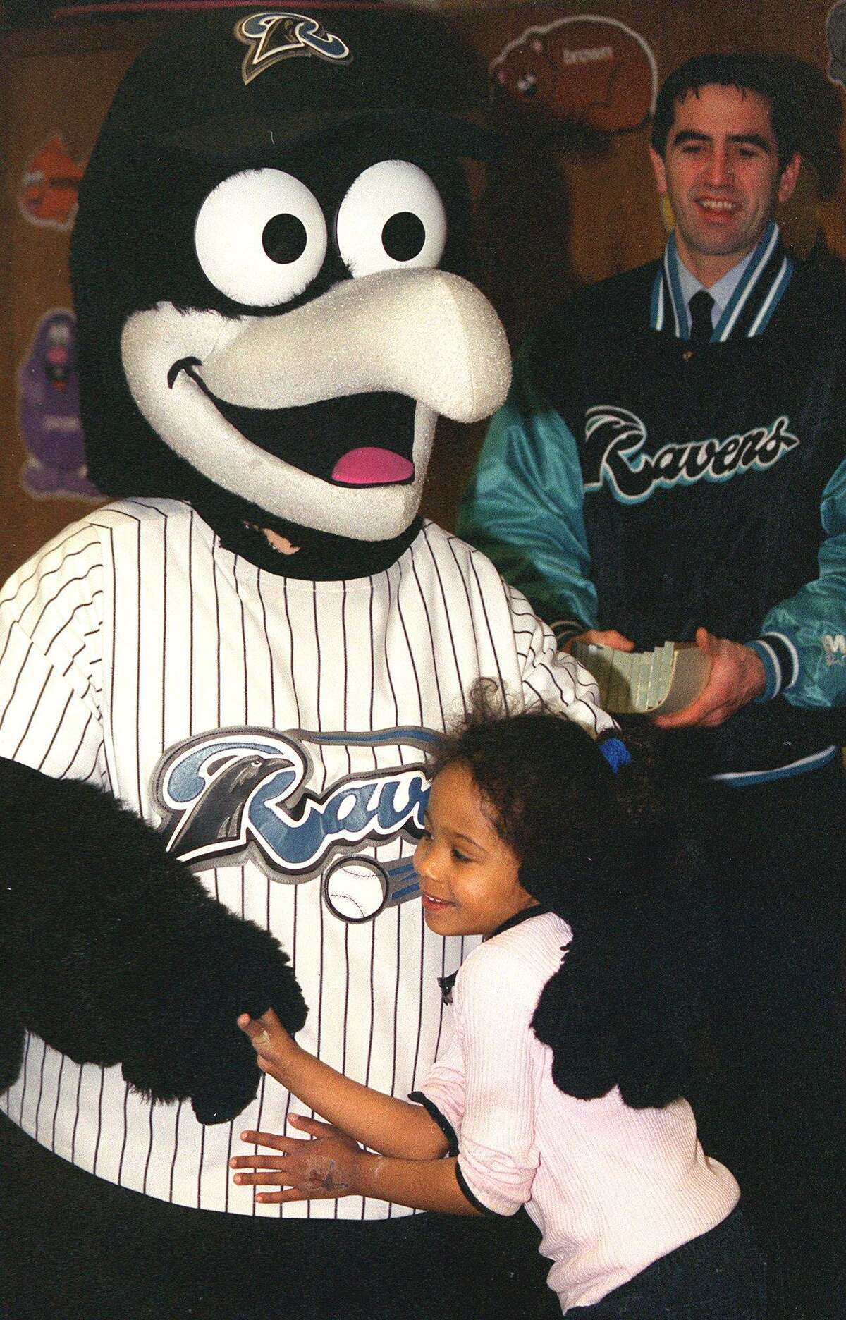 """In this file photo, SPECTRUM/Northville Elementary School student Brianna Jackson hugs Rally, the New Haven Ravens' mascot, during the school's """"Rally Around Reading"""" literature week."""
