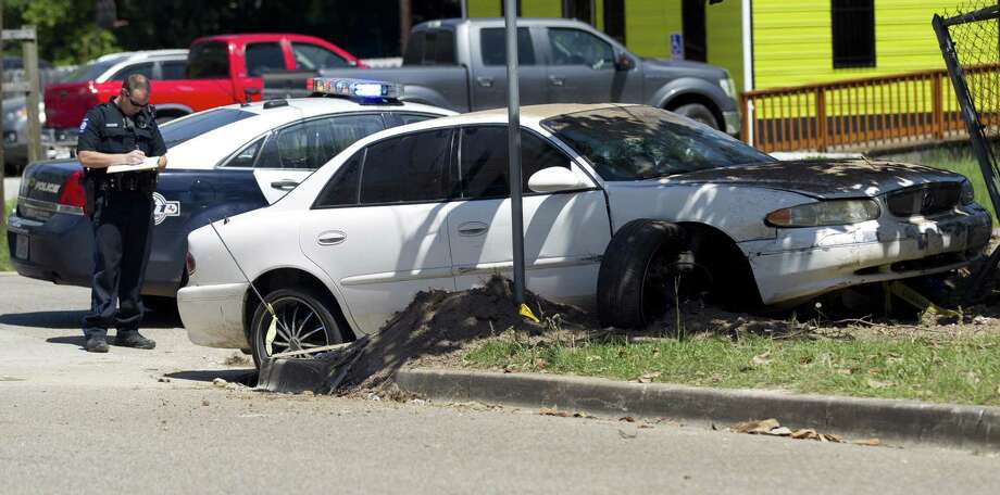 A Conroe police officer works the scene of a car crash after a high-speed pursuit ended at 1st Street and East Ave. I on Wednesday, May 16, 2018, in Conroe. The chase lead law enforcement through downtown Conroe following a traffic-stop. Photo: Jason Fochtman, Staff Photographer / Houston Chronicle / © 2018 Houston Chronicle