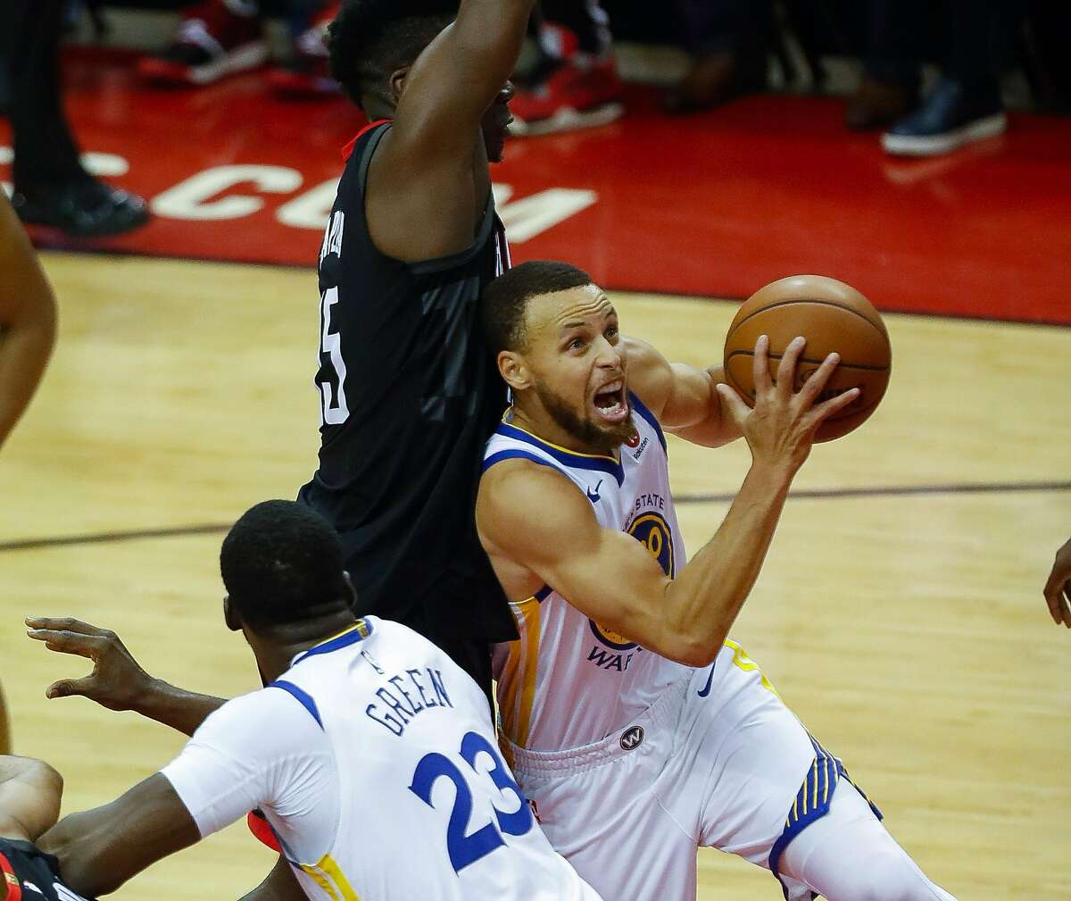 Golden State Warriors guard Stephen Curry (30) shoots around Houston Rockets center Clint Capela (15) during Game 2 of the Western Conference Finals at the Toyota Center, Wednesday, May 16, 2018, in Houston.