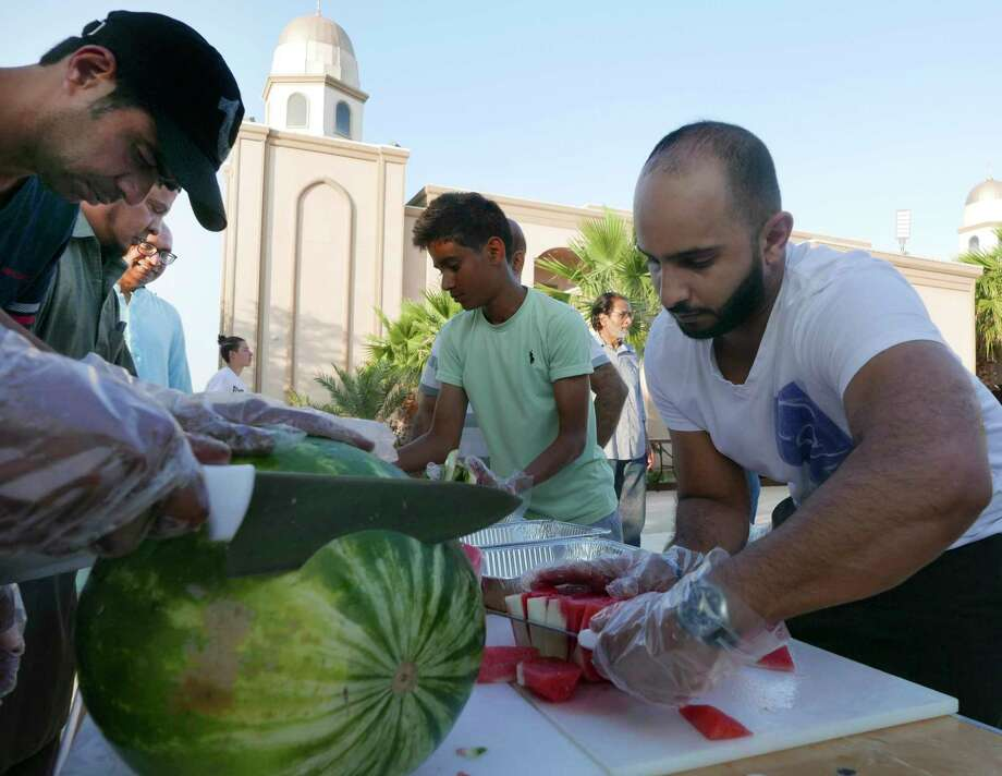 Hassan Babar, left, and Fahad Alqahtani, right, slice watermelons for the break fast meal at the Muslim Children Education and Civic Center on Wednesday, May 16, 2018, which is the first day of Ramadan, a month of prayer, dawn-to-dusk fasting and feasts which begin after sunset. The MCECC is one of the city's largest mosques. There are an estimated 30,000 Muslims in San Antonio. Photo: Billy Calzada, San Antonio Express-News / San Antonio Express-News