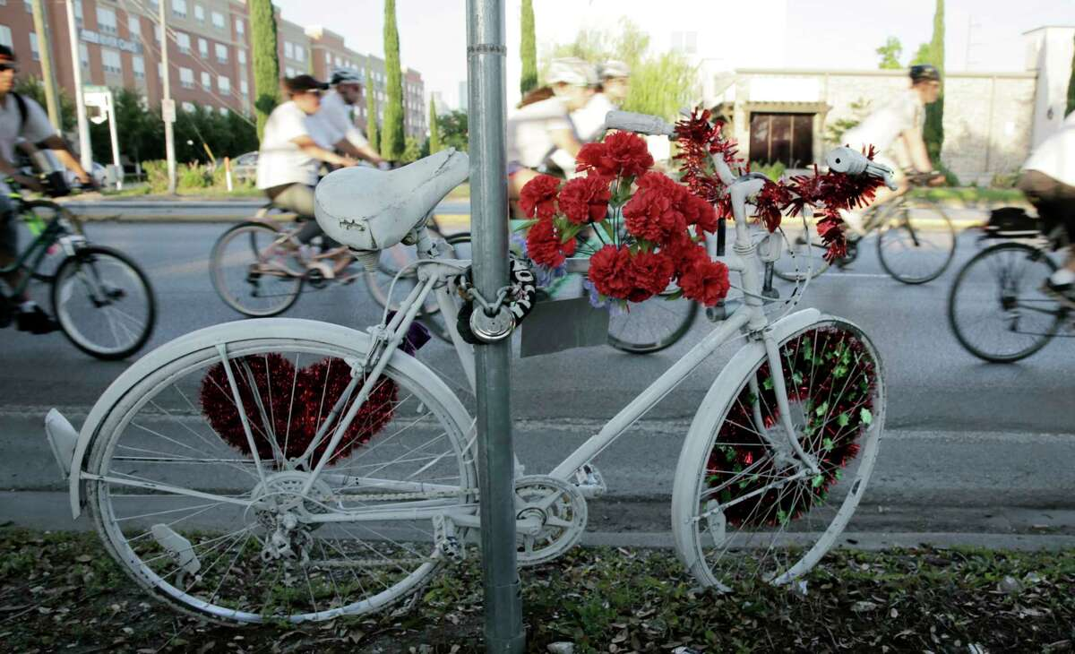 """Area cyclist ride past a ghost bike dedicated to Chelsea Norman, who was killed by a driver while riding her bike in 2013, during a 10-mile route in silence on Wednesday, May 16, 2018 in Houston. The riders were joining other cyclists worldwide in the """"Ride of Silence"""" to bring attention to those who have died while riding their bicycles on local roads."""