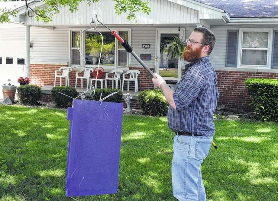 Extension educator Ken Johnson prepares to place an Emerald ash borer trap in an ash tree Wednesday. Photo:       Nick Draper | Journal-Courier