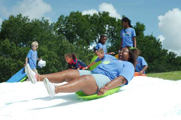 Counselor Aspen Smith demonstrates proper snow sledding technique during last year's Champion Kids Camp in Alvin. A June 3 concert will benefit the camp for children who have experienced traumatic injury, illness or personal loss.