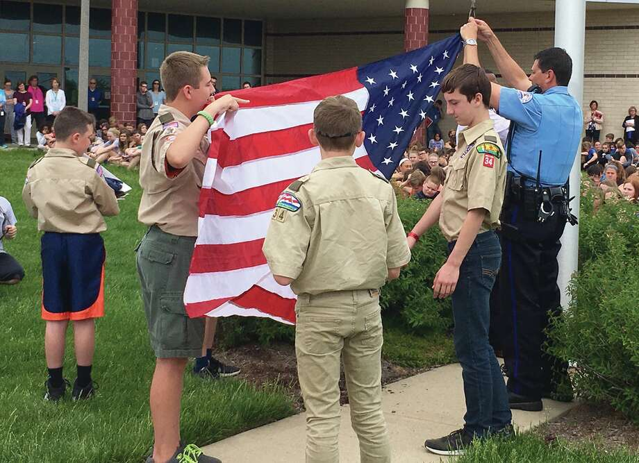 Boy Scouts work to hoist the American Flag.