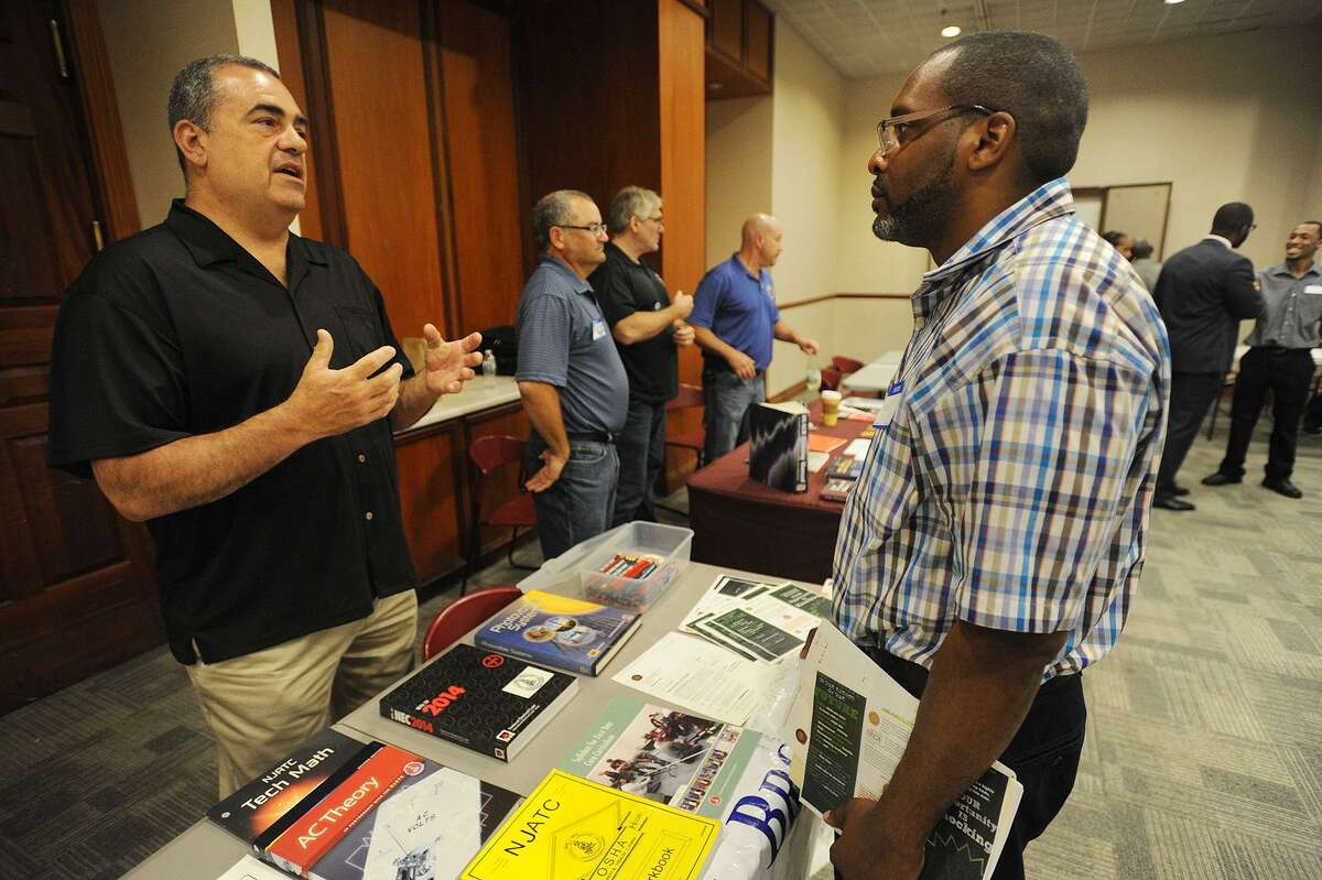 Sean Toliver, right, of Bridgeport, talks with Thomas Sportini, training director for IBEW Local 488 electrical workers union, at the Bridgeport Re-Entry Career Fair, at the Margaret Morton Government Center in Bridgeport, Conn., on June 28, 2017.
