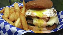 A Folc Burger with cheese, a fried egg, pork belly and Folc sauce with fries from Bexar Pub.