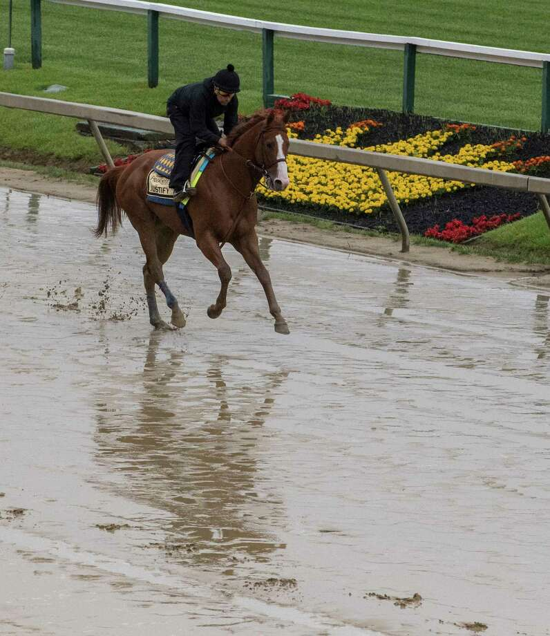 Kentucky Derby winner Justify gallops over the muddy track for his morning exercise at Pimlico Race Course in preparation for Saturday's Preakness Stakes Thursday May 17, 2018 in Baltimore, MD (Skip Dickstein/Times Union) Photo: SKIP DICKSTEIN, Albany Times Union