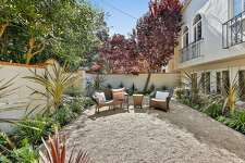 Established plantings surround a pebble patio behind the Marina District home.