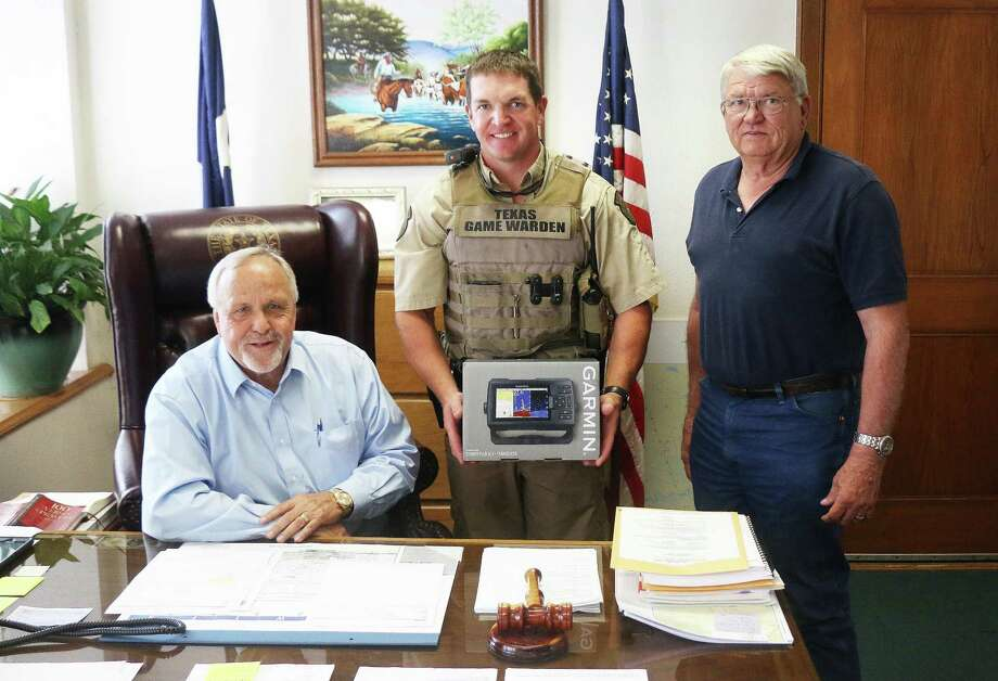 Liberty County Judge Jay Knight (seated) and Pct. 2 Commissioner Greg Arthur (right) present Texas Game Warden Jake Noxon with a depth-finder and GPS for his boat. Photo: David Taylor / HCN