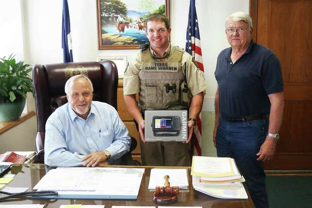Liberty County Judge Jay Knight (seated) and Pct. 2 Commissioner Greg Arthur (right) present Texas Game Warden Jake Noxon with a depth-finder and GPS for his boat.