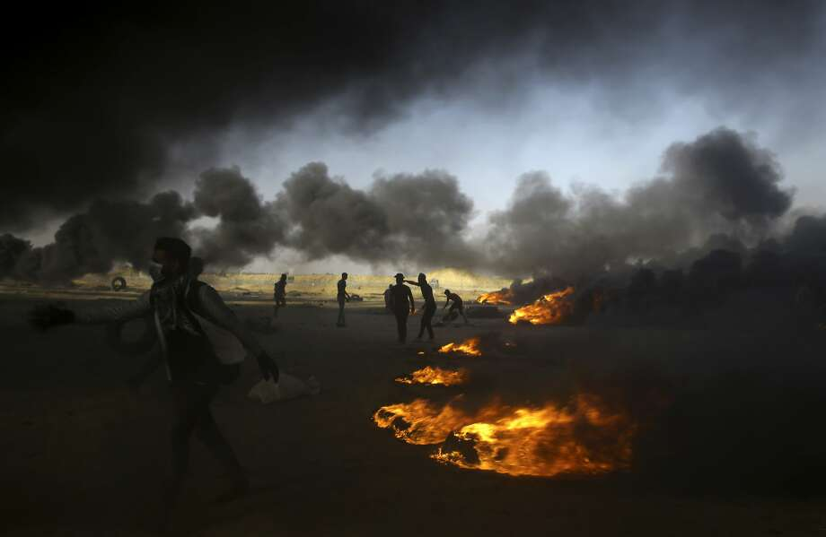 "FILE - In this Tuesday, May 15, 2018 file photo, Palestinian protesters burn tires at the Gaza Strip's border with Israel, east of Khan Younis. The aftershocks of the U.S. Embassy move to Jerusalem and bloodshed on the Gaza border are shaking up the region, including the relationship between Palestinian President Mahmoud Abbas and former his negotiating partners, Israel and the U.S. Seething over a perceived U.S. betrayal on Jerusalem, Abbas is preparing to pursue what has been called his ""doomsday weapon,"" a war crimes complaint against Israel at the International Criminal Court. (AP Photo/Adel Hana, File) Photo: Adel Hana, Associated Press"