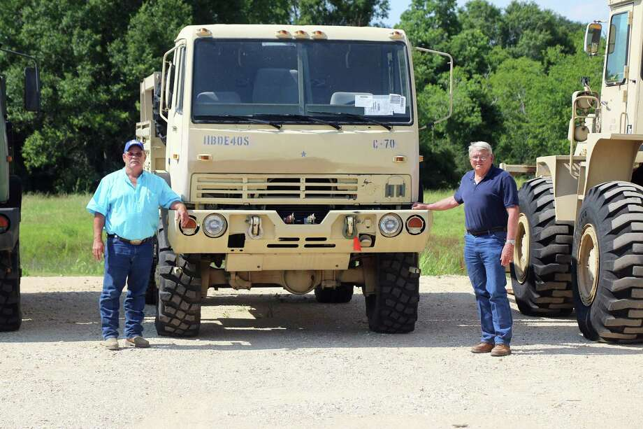 Pct. 1 Commissioner Bruce Karbowski, left, and Pct. 2 Commissioner Greg Arthur stand next to one of the military Light Medium Tactical Vehicle's purchased for high-water rescues should the county endure another flood. Photo: David Taylor / HCN