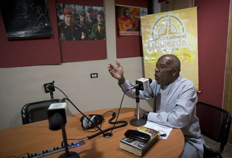 In this April 6, 2018 photo, Hector Madera hosts his two-hour pro-government radio talk show in the neighborhood of San Agustin in Caracas, Venezuela. Madera is confident that 10 million revolutionaries will turn up on election day on May 20 to propel President Nicolas Maduro forward in an honest and fair contest, explaining that they're not voting for the man, but rather the embodiment of Hugo Chavez's ideals representing a battle to liberate Venezuela from capitalism's grasp. (AP Photo/Ariana Cubillos) Photo: Ariana Cubillos / Associated Press