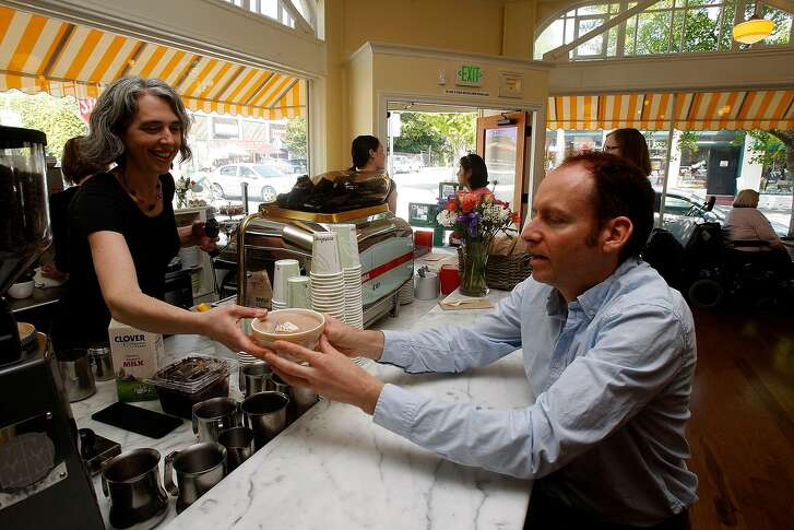 General manager Kara Hammond (left) handing owner Michael Pearce (right) a hot chocolate at Elmwood Cafe in Berkeley, Calif., on Friday, April 23, 2010.