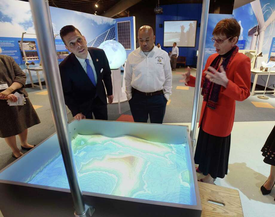 Assemblymember Angelo Santabarbara, left, Assembly Speaker Carl Heastie, center, and Gina Gould, president of miSci, look over the augmented reality sandbox, where visitors can hold their hand over the sand and see how rain would fall on the landscape, during a tour of the museum on Thursday, May 17, 2018, in Schenectady, N.Y. Speaker Heastie is starting his third annual series of visits to all of the Assembly districts. Speaker Heastie started this year's visits at miSci.  Currently on display at the museum are Invention Convention items, items designed by students to solve an everyday problem. The museum will host an actual invention convention on Thursday, May 24th from 5:00pm to 7:00pm. The mockups of inventions created by K through eighth grade students can be seen at the museum. This Saturday the interactive exhibit, Brain: The World Inside Your Head opens up and runs through the summer. By mid-summer the museum will also break ground on The Dudley Observatory at miSci.    (Paul Buckowski/Times Union) Photo: PAUL BUCKOWSKI, Albany Times Union / (Paul Buckowski/Times Union)