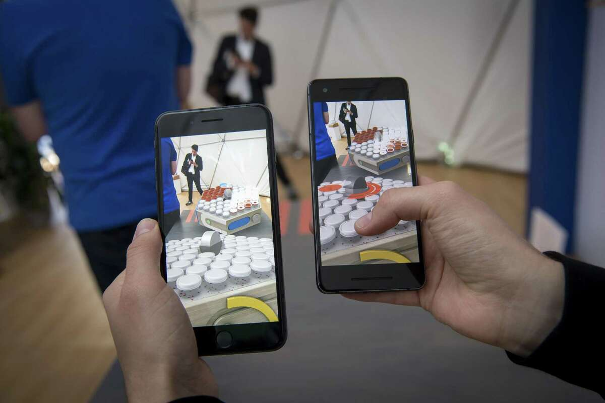An exhibitor demonstrates a multiplayer augmented reality game using a shared cloud space that can be played between both Apple iPhones operating iOS and GoogleAndroid smartphones during the Google I/O Developers Conference in Mountain View, California, U.S., on Tuesday, May 8, 2018. Stamford-based Charter Communications is planning to enter the mobile market, with its Spectrum Mobile service, before the end of 2018.