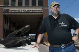 Gregory Pierce stands outside the University of Houston- Downtown, beside a sculpture of a gator, the mascot for UHD.