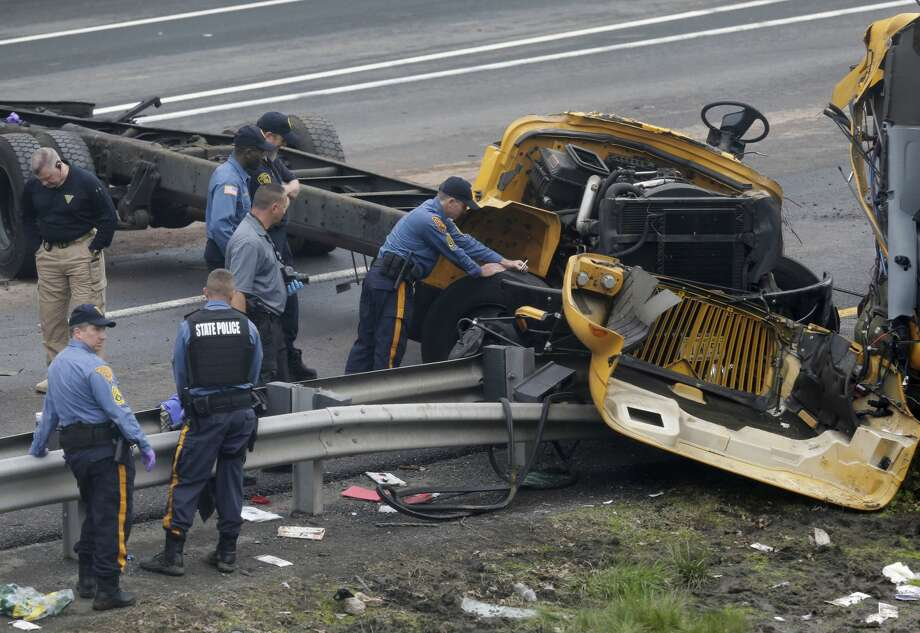 Emergency personnel examine a school bus after it collided with a dump truck, injuring multiple people, on Interstate 80 in Mount Olive, N.J., Thursday, May 17, 2018. (AP Photo/Seth Wenig) Photo: Seth Wenig/AP
