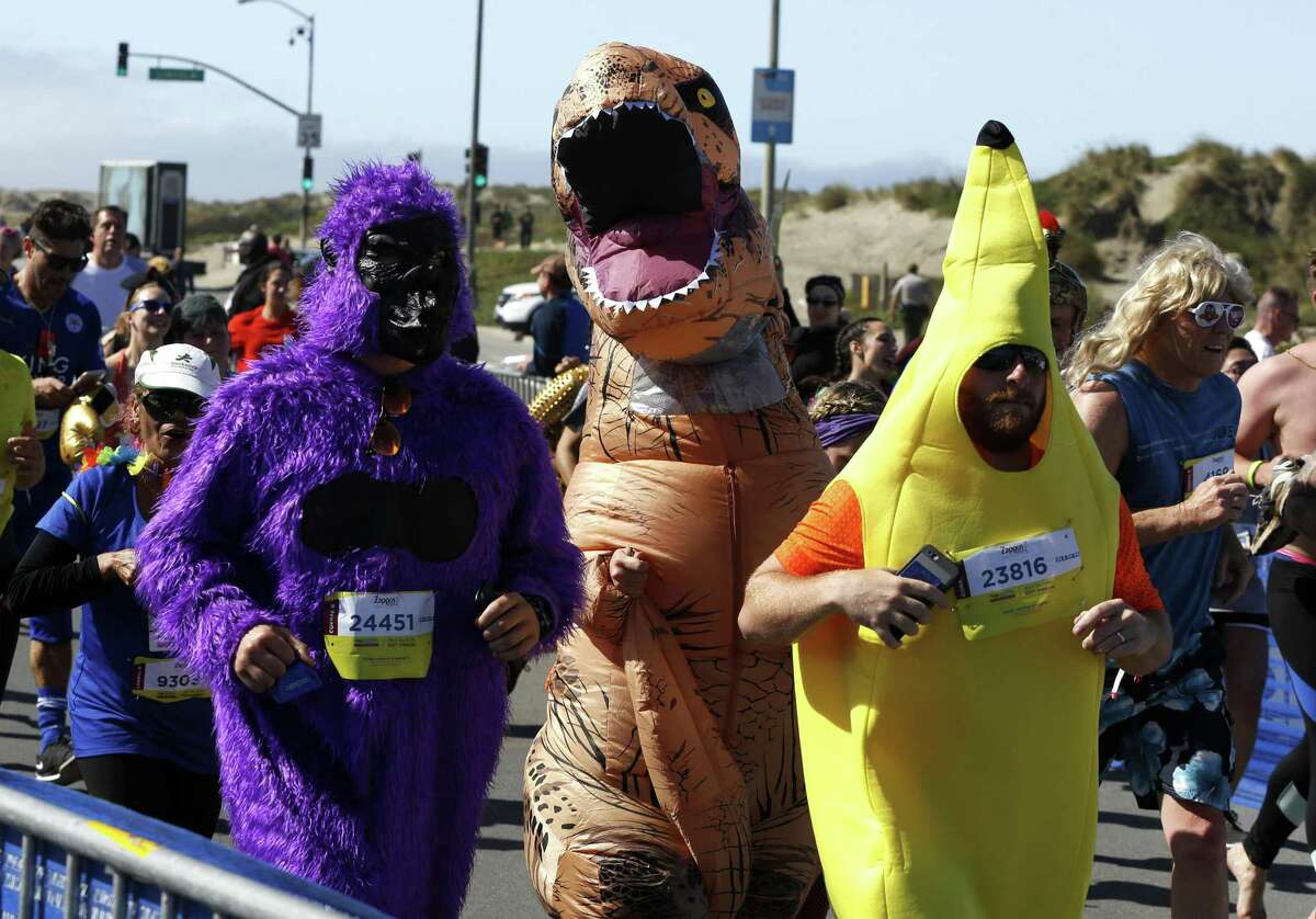 A purple gorilla, t-rex and yellow banana run the Bay to Breakers race in San Francisco, California, on Sunday, May 15, 2016.