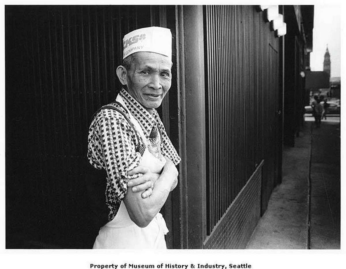 In this image, Nariano Chachero, a Filipino dishwasher at the Tai Tung restaurant in Seattle's vibrant and multi-cultural International District, takes a rest from his work for a breath of fresh air, July 8, 1988. In the distance behind Mr. Chachero the King Street Station clock tower is visible.