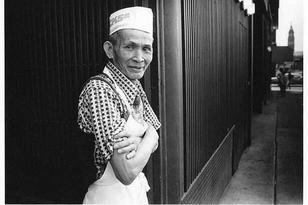 In this image, Nariano Chachero, a Filipino dishwasher at the Tai Tung restaurant in Seattle's vibrant and multi-cultural International District, takes a rest from his work for a breath of fresh air, July 8, 1988. In the distance behind Mr. Chachero the King Street Station clock tower is visible.  Courtesy of MOHAI, Photo by Jennifer Werner Jones, Seattle Post-Intelligencer