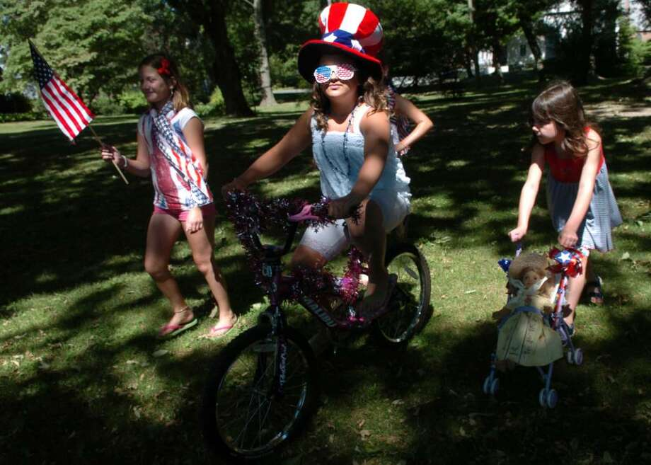 Nine-year-old Caitlin Golynker is decked out in red, white and blue as she rides her bike around the Fairfield town green Saturday July 3, 2010 during the Patriotic Parade hosted by the Fairfield Museum and History Center. Photo: Autumn Driscoll / Connecticut Post