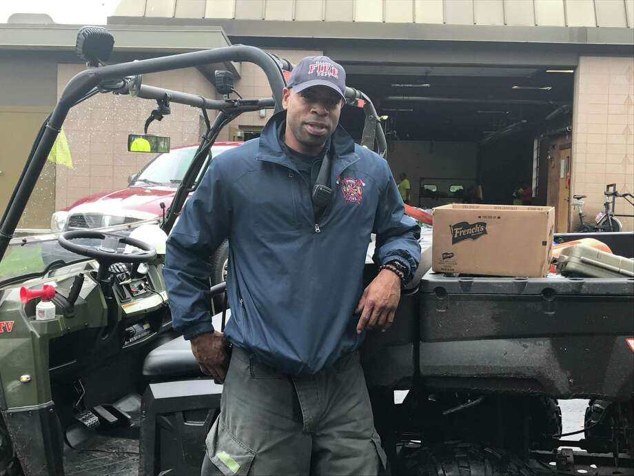 Firefighter/EMT Danny Mota stands in front of the department's ATVs. Photo: Jessica Lerner / Hearst Connecticut Media