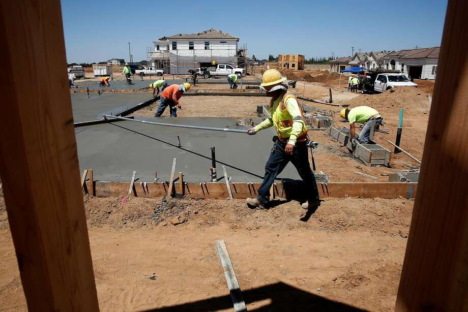 Workers construct homes at the De Young EnVision development in Clovis (Fresno County). The planned community will feature 36 zero net energy homes, which generate as much electricity as they consume. Photo: Photos By Michael Macor / The Chronicle