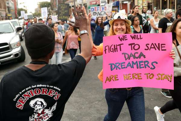 af8cf3337cad0a 2of2Allison Banks of Berkeley high fives a man as a protest march heads  down Durant Avenue during pro-DACA rally in Berkeley, Calif., on Tuesday,  ...