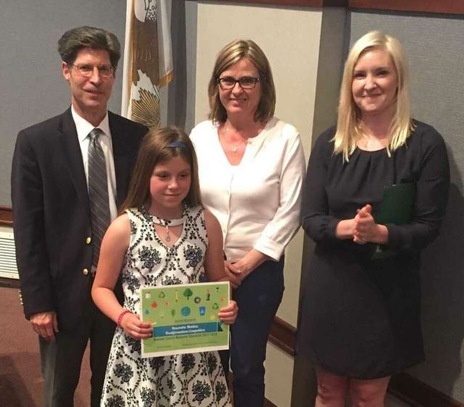 Madison County Board Chairman Kurt Prenzler, County Board member Ann Gorman and Resource Education Program Coordinator Eve Drueke present Annie Bozarth of Edwardsville's Woodland Elementary School with a certificate of recognition for the trashformation competition. Photo:       For The Telegraph