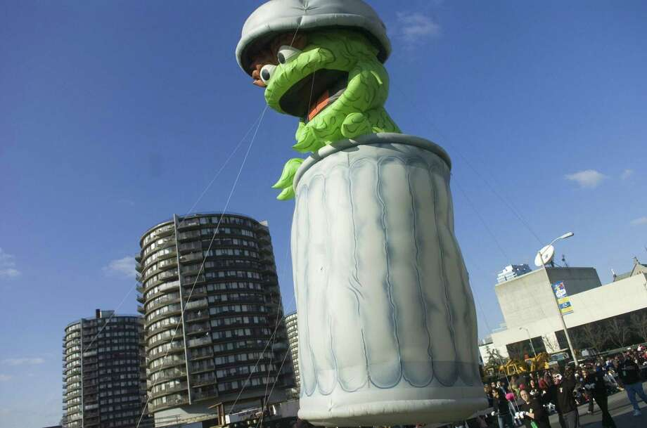 Oscar the Grouch heads down Atlantic St. during the UBS Parade Spectacular in Stamford in 2009. St. John's Towers loom in the background. Photo: Staff File Photo