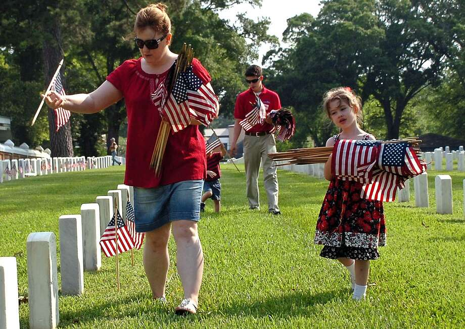 Aided by her daughter, the wife of a Marine places U.S. flags on the graves at Alexandria National Cemetery in Pineville, La., for Memorial Day. 2012. Photo: Melinda Martinez /AP / The Daily Town Talk
