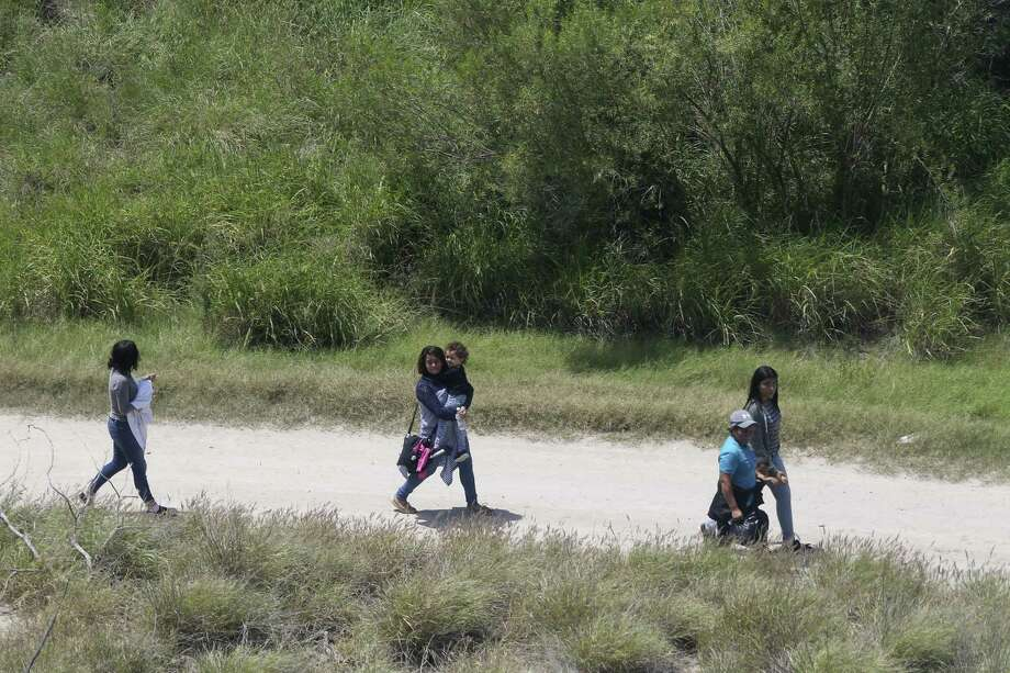 A group of immigrants, including children, walk along a road minutes after smugglers rafted them across the Rio Grande into the U.S. at a site called El Rincon in Hidalgo County on Friday. The administration plans to separate parents from their children. Photo: JERRY LARA /San Antonio Express-News / San Antonio Express-News