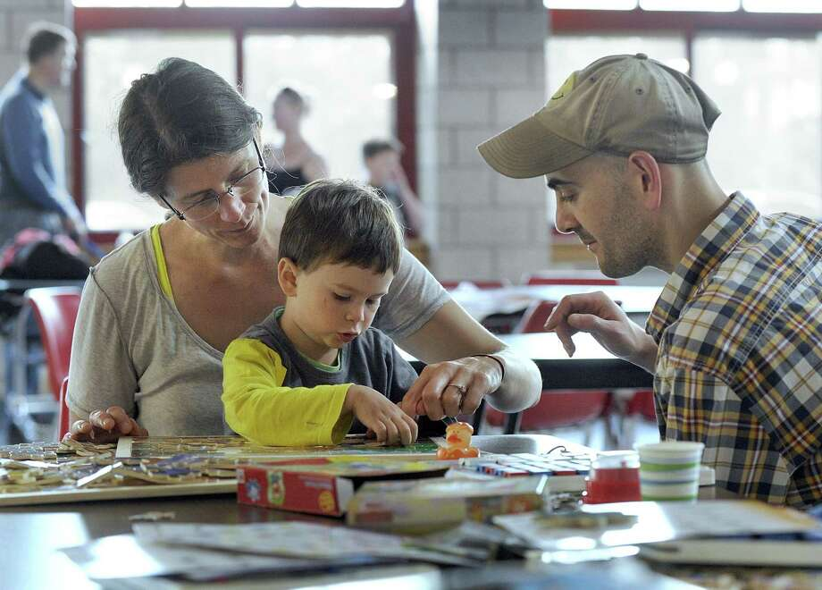 Rebecca and Eddie Bacigalupo do a puzzle with son Arthur, 3, at  New Fairfield High Thursday, May 18, 2018. The high school is being used as a shelter for residents like the Bacigalupos who lost power during Tuesday's storm. Photo: Carol Kaliff / Hearst Connecticut Media / The News-Times