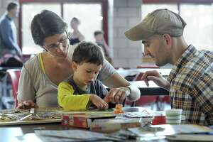 Rebecca and Eddie Bacigalupo do a puzzle with son Arthur, 3, at  New Fairfield High Thursday, May 18, 2018. The high school is being used as a shelter for residents like the Bacigalupos who lost power during Tuesday's storm.
