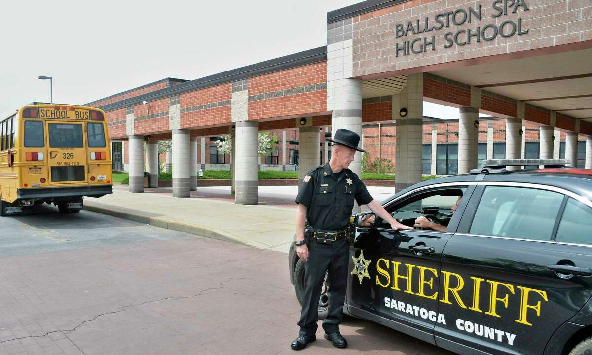Saratoga County Sheriff director of community preparedness and youth services, Deputy Ken Cooper,center, speaks with Deputy Biagio Guida outside Ballston Spa High School Thursday May 17, 2018 in Ballston Spa, NY. Seven county schools have signed up to have trained and armed resource officers walk their corridors. (John Carl D'Annibale/Times Union)