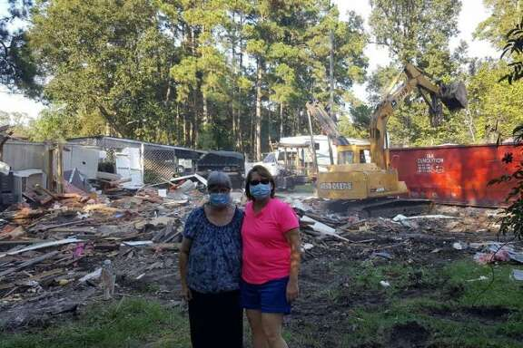 Darlene Bradbery and Stacy Christ stand on Bradbery's property in Huffman as her house is demolished due to flood damage from the Tax Day flood in 2016.