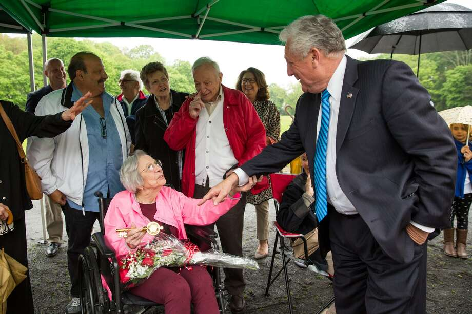 "Norwalk Mayor Harry Rilling awards Louise Esposito, widow to the late Mayor Frank J. Esposito with the key to the city during an honorary ceremony for Mayor Esposito in Norwalk, Conn. on Thursday, May 17, 2018. Blue signs reading ""Honorable Frank J. Esposito Way"" were added below the existing green ""City Hall Dr"" signs at Eversley Avenue and Sunset Hill Avenue, as well as in front of the City Hall field. Photo: Chris Palermo / For Hearst Connecticut Media / Norwalk Hour Freelance"