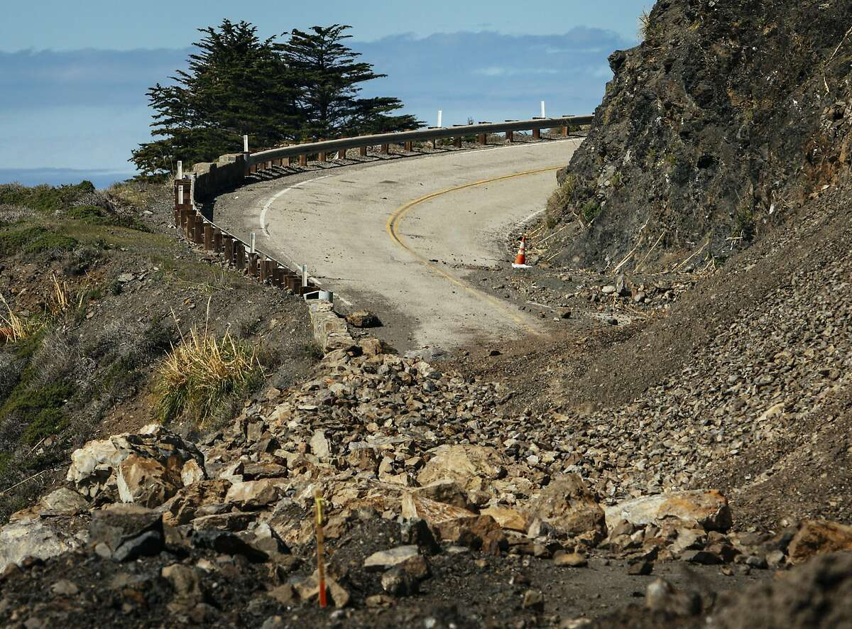 FILE-- In a March. 8, 2018 photo, the work road near the north side of Highway 1 is covered in debris as work above the road continues to release loose debris as part of the construction process at the Mud Creek Slide on the Big Sur Coast of Calif. The stretch of Highway 1 just south of Pfeiffer Big Sur State Park will reopen in July - two months earlier than expected after a year-plus closure due to a massive landslide, Caltrans said.