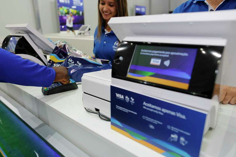 """In this June 30, 2016, image taken by AP Images for Visa, Team Visa athlete Popole Misenga uses his Visa payment ring at the Copacabana Megastore in Rio de Janeiro, Brazil.  Payment networks and manufacturers are building payment functions into more devices — expanding your options as well as freeing up your hands. Connected """"smart"""" accessories such as watches, bands and rings travel lighter than a phone. To use, the wearer holds a wrist or hand up to a contactless payment terminal. Visa tested these devices at the 2016 Rio Olympics to demonstrate possibilities, says Mark Jamison, global head of innovation and design at Visa. (Leo Correa/AP Images for Visa) Photo: Leo Correa / AP Images"""