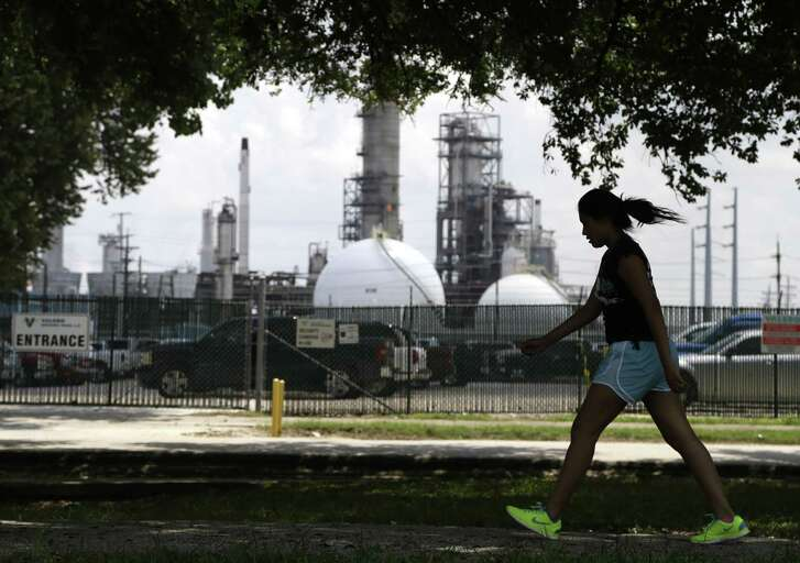 A teenage girl walks around the track of a park across the street from the Valero refinery Monday, Aug. 4, 2014, in the Manchester neighborhood of Houston.