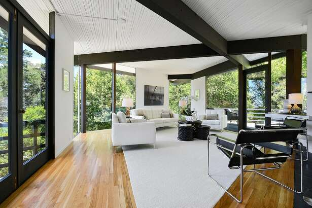 Floor-to-ceiling windows surround the living room.
