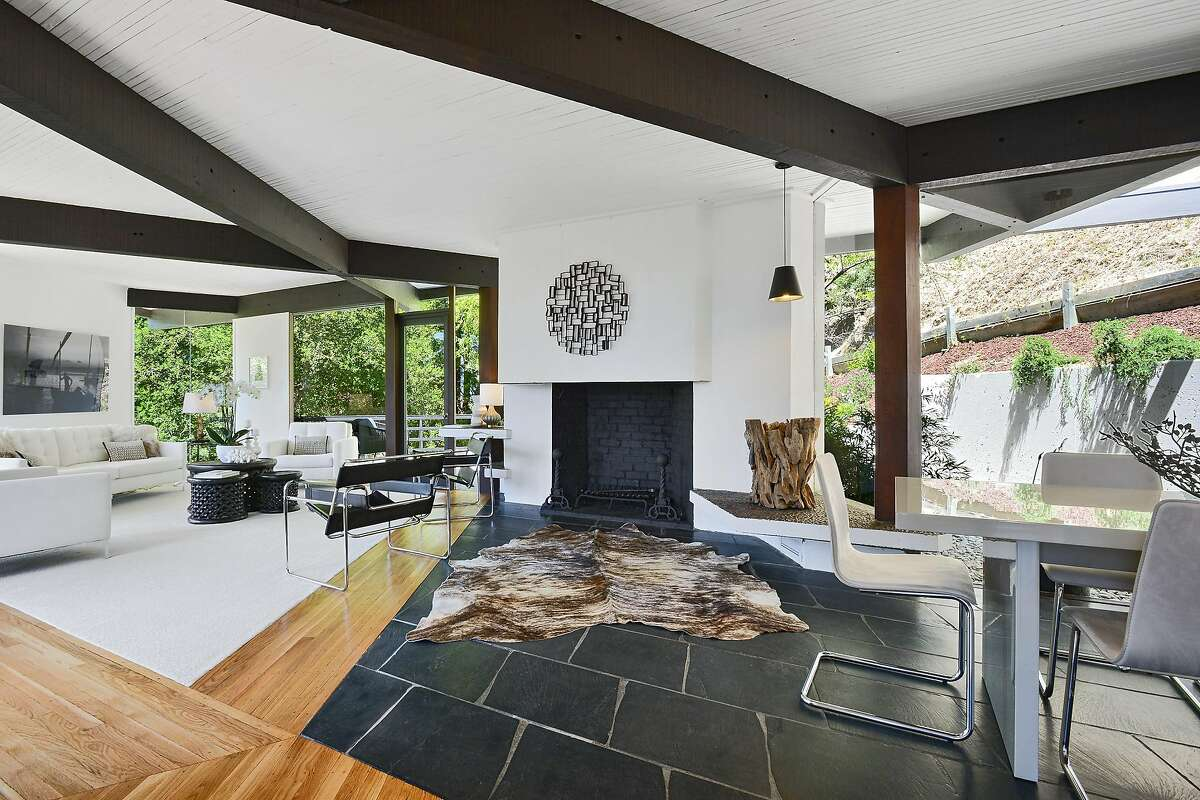 The living room features a beamed ceiling and a wood-burning fireplace.