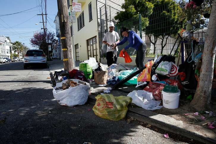 Ed helps out his friend Sandra clean up after a night on the streets at the corner of Hampshire and 26th streets in the Mission neighborhood in San Francisco, Ca. on Mon. May 7, 2018.