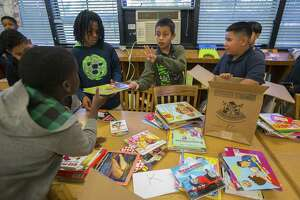 Oscar Mendez, 11, center, helps his fellow fifth graders sort library books into grade level groups inside the library at Kelso Elementary School, Thursday, May 17, 2018, in Houston. The library is cooled by a window unit air conditioner. Houston Independent School District administrators are making an initial recommendation that the district seek a $1.7 billion capital projects bond vote in May 2019 that would help replace schools like Kelso.  ( Mark Mulligan / Houston Chronicle )