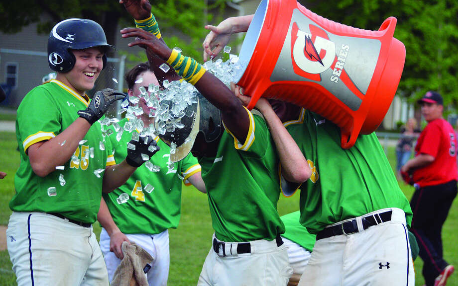 Metro-East Lutheran's Darion Brooks, middle, gets doused with a bucket of ice water by his teammates after Brooks had the game-winning hit in Thursday's Class 1A regional semifinal against Bunker Hill.