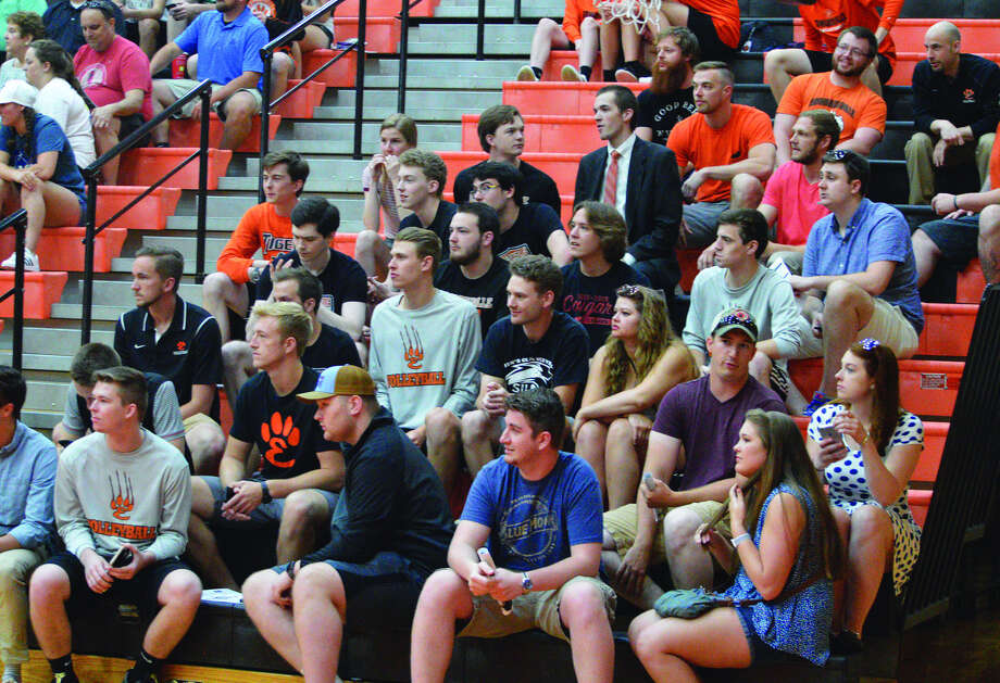 Former players of the Edwardsville boys' volleyball team watch the current Tigers sweep past Belleville West in the regular season finale on Tuesday.