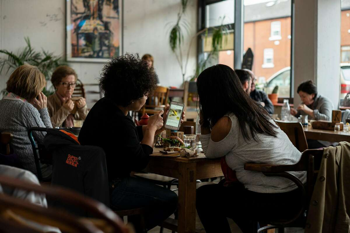 People in a coffee shop in central Dublin, Ireland, May 5, 2018. Ireland is the European headquarters for other data-hungry companies including Airbnb, Apple, Facebook, Google, Twitter and Microsoft, which owns LinkedIn. With Europe�s sweeping new data privacy law, Ireland is in the middle of a standoff between regulators and tech companies. (Paulo Nunes dos Santos/The New York Times)