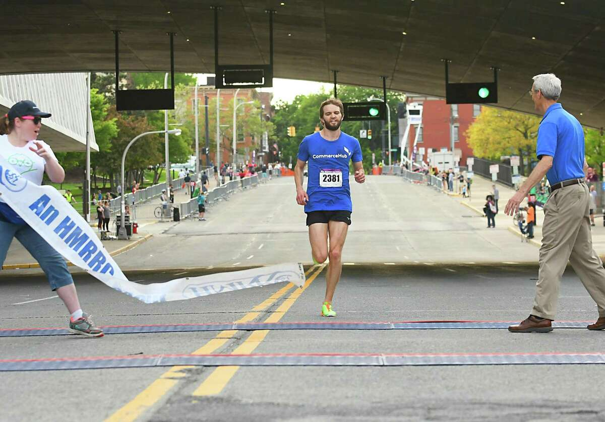 Albany resident Matt Brooker running for CommerceHub, crosses the finish line in first place during the CDPHP Workforce Team Challenge 5K on Thursday, May 17, 2018 in Albany, N.Y. (Lori Van Buren/Times Union)